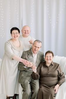 Gelukkige familie, hoger paar en paar van middelbare leeftijd, poseren voor foto in de kersttijd