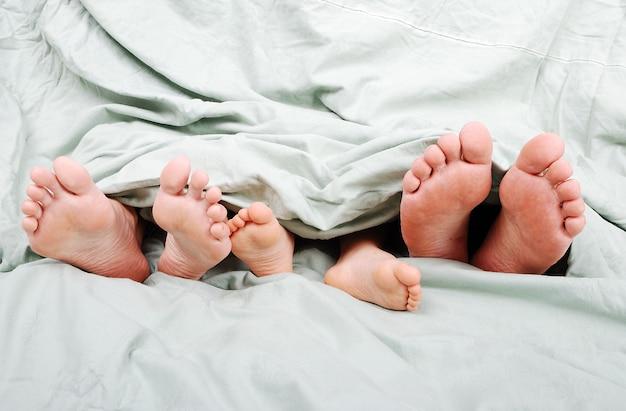 Gelukkige familie in bed onder de deken