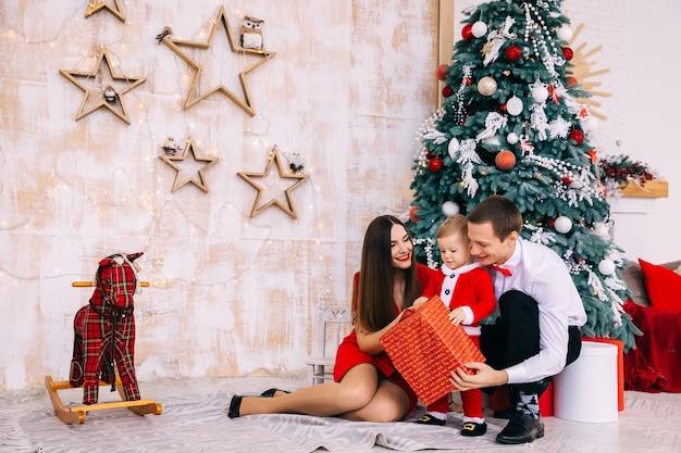 Gelukkige familie in de buurt van de kerstboom geschenken uitpakken. baby in santakostuum. hobbelpaard.