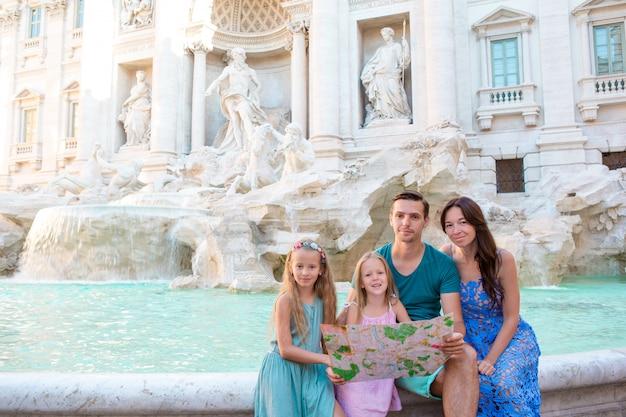 Gelukkige familie in de buurt van fontana di trevi met stadskaart
