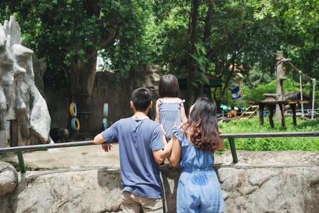 Gelukkige familie in de dierentuin die naar een beer kijkt