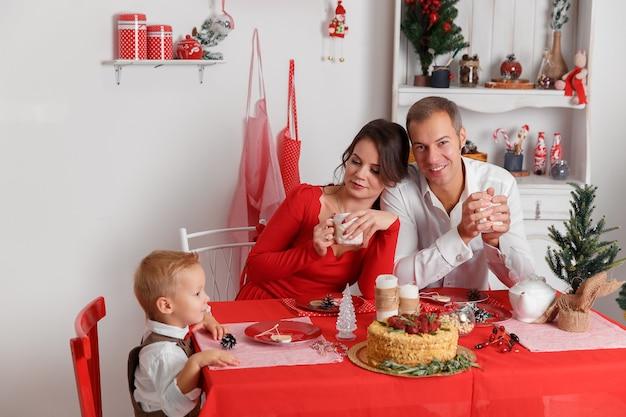 Gelukkige familie in de keuken en het drinken van thee. lekkere kersttaart op tafel. nieuwjaarsvakantie en plezier.