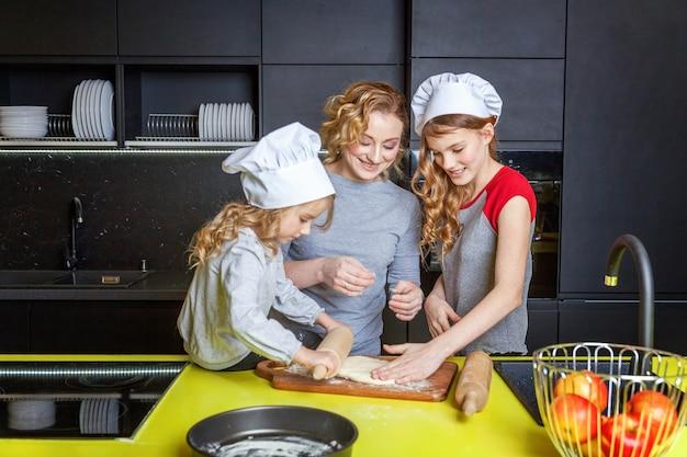 Gelukkige familie in de keuken. moeder en twee kinderen deeg bereiden, appeltaart bakken. moeder en dochters koken thuis gezond eten en hebben plezier. huishouden, teamwerk helpen, zwangerschapsconcept