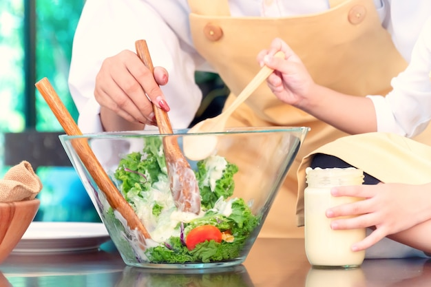 Gelukkige familie in de keuken. moeder leert zoon om gezond voedsel te koken in de zomervakantie.