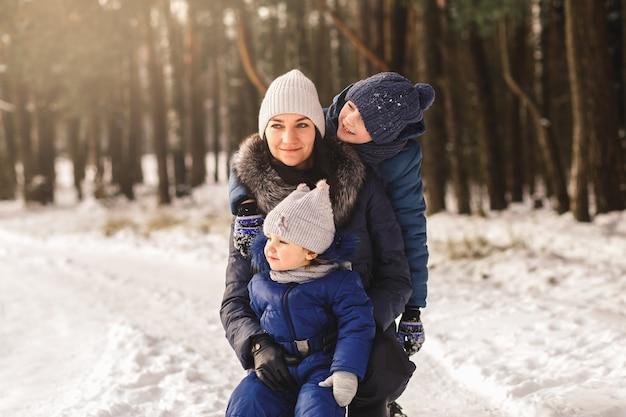 Gelukkige familie in de winter tijdens een wandeling in het bos. moeder met kinderen