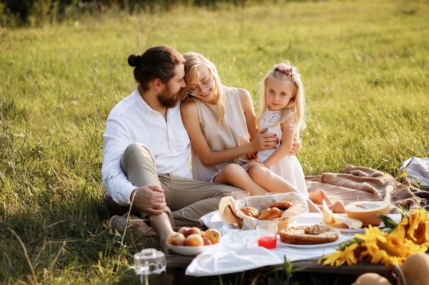 Gelukkige familie in de zomer bij zonsondergang