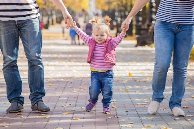 Gelukkige familie in dezelfde kleren voor een wandeling in het park in de herfst