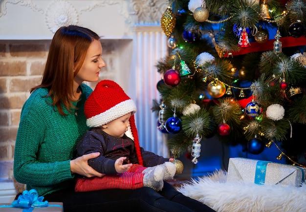 Gelukkige familie in een interieur op de achtergrond van de kerstboom met geschenken