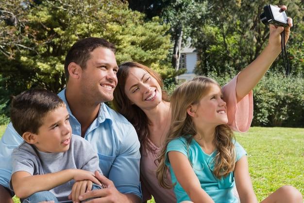 Gelukkige familie in een park dat foto's neemt