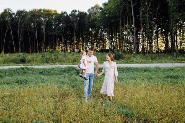 Gelukkige familie in een park in de zomer de herfst. moeder, vader en baby spelen in de natuur in de stralen van de zonsondergang