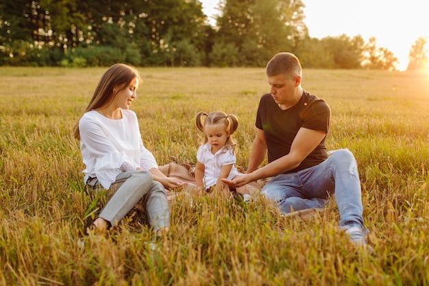 Gelukkige familie in een veld in de herfst. moeder, vader en baby spelen in de natuur in de stralen van de zonsondergang