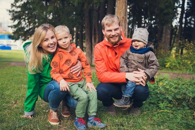 Gelukkige familie in herfst bos - ouders en kinderen glimlachen