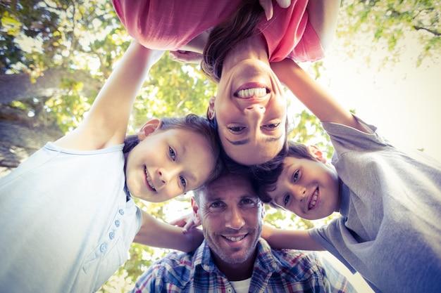 Gelukkige familie in het park die in cirkel samenweken