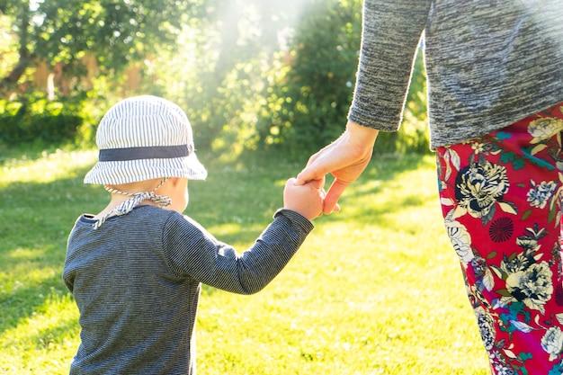 Gelukkige familie in het park. moeder en baby lopen bij zonsondergang. moeder houdt de hand van de baby vast.