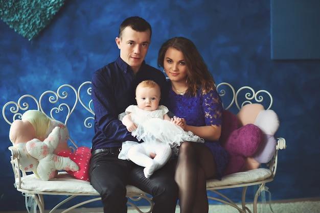 Gelukkige familie in interyerniy. vader, moeder en baby zijn blij. ontspan op een bankje