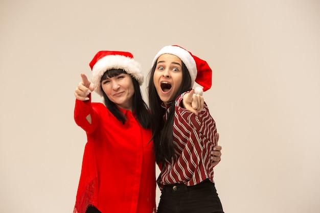 Gelukkige familie in kerstmissweater poseren. genieten van liefdesknuffels, vakantiemensen. moeder en dochter op een grijze achtergrond in de studio