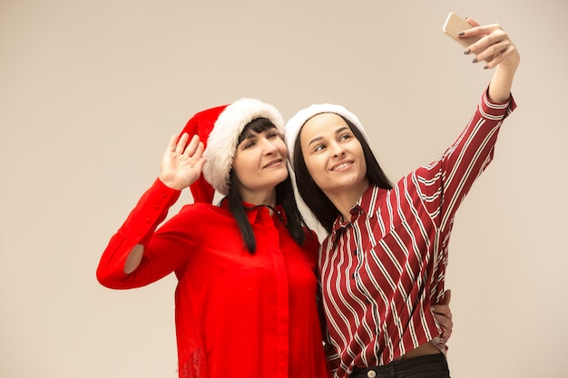 Gelukkige familie in kerstmissweater poseren met mobiele telefoons