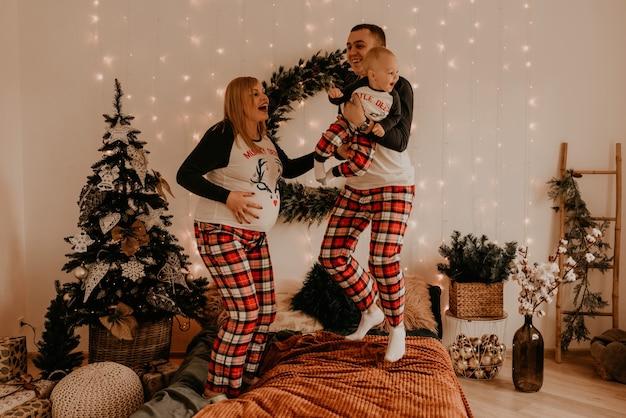 Gelukkige familie in pyjama's met childparents spelen met kind springen op bed in de slaapkamer. familiekleding voor het nieuwe jaar ziet eruit als outfits. valentijnsdag viering geschenken