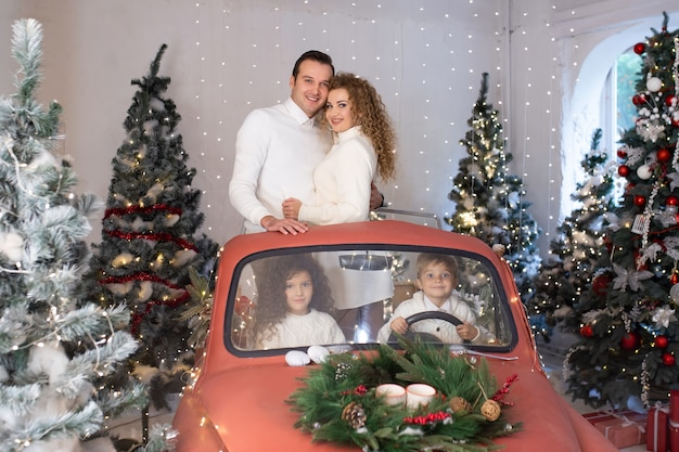 Gelukkige familie in rode auto dichtbij kerstbomen. samen genieten op vakantie.