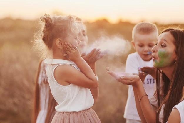 Gelukkige familie is besmeurd met verf. kinderen spelen met holi-festivalkleuren. concept voor indiase festival holi. nationaal, familiefeest, selectieve aandacht