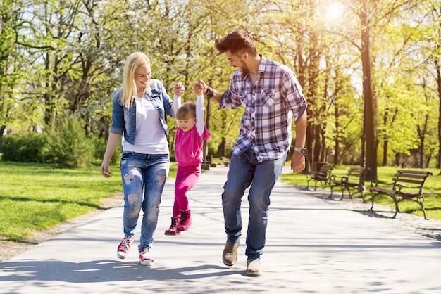 Gelukkige familie, jonge kaukasische ouders die met hun dochter in een park wandelen