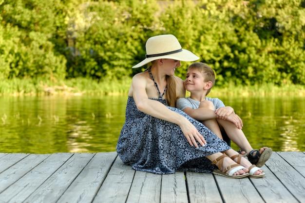 Gelukkige familie, jonge moeder met haar zoontje zitten op de pier bij de rivier