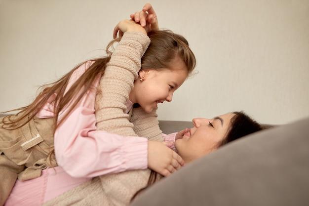 Gelukkige familie jonge volwassen bovenliggende moeder en schattige tiener schoolmeisje binding, praten, genieten van zoete moment ontspannen liggend in bed
