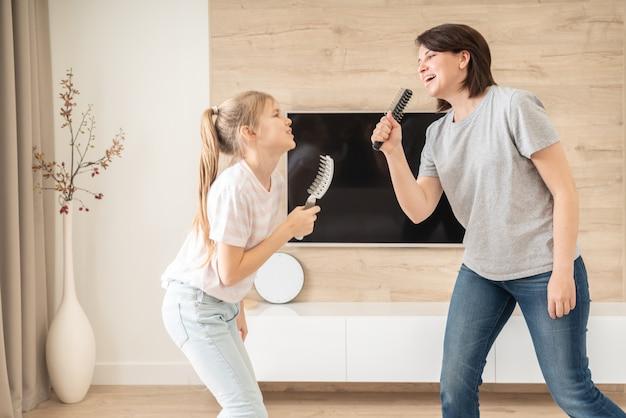 Gelukkige familie jonge volwassen moeder en schattige tiener dochter plezier zingen karaoke lied in haarborstels.