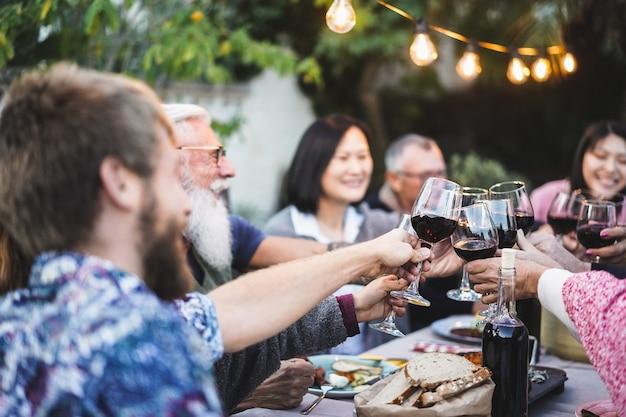 Gelukkige familie juichen met rode wijn bij barbecue diner buiten - verschillende leeftijden van mensen die plezier hebben tijdens weekendmaaltijd - voedsel- en zomerconcept - focus op close-up glas
