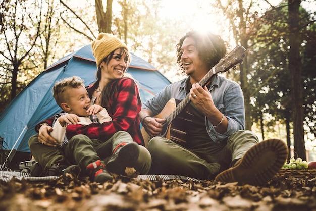 Gelukkige familie kamperen in het bos gitaar spelen en samen zingen - moeder, vader en zoon hebben plezier trekking in de natuur zittend voor de tent - familie, natuur en trekking concept
