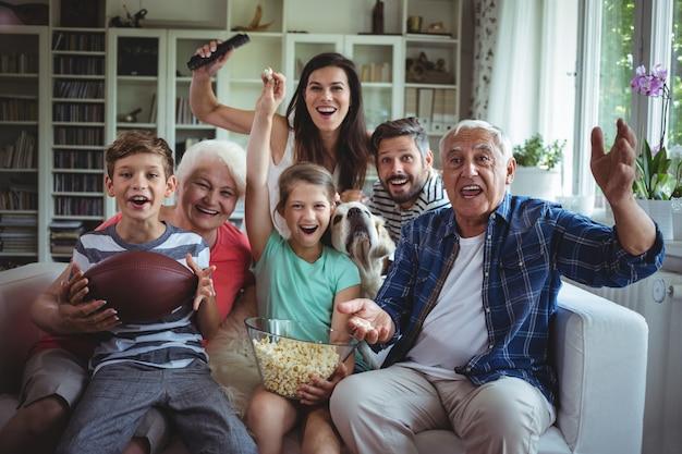 Gelukkige familie kijken naar voetbalwedstrijd op televisie in de woonkamer