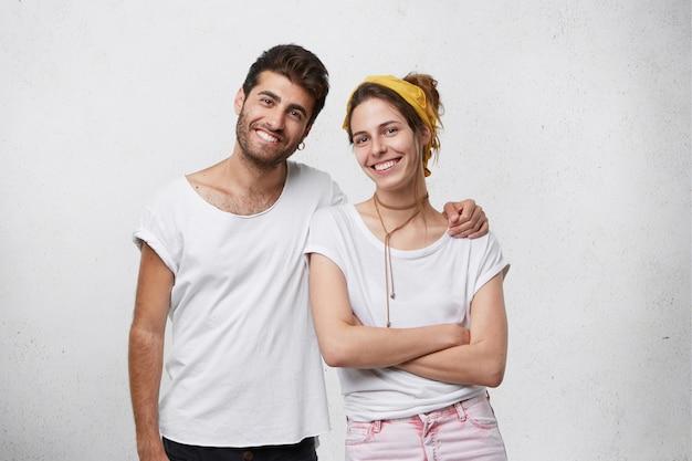 Gelukkige familie: knappe bebaarde man die zijn vrouw met liefde omhelst die gekruiste handen staat en glimlachend blij is om de zorg van haar man te voelen. jonge mensen knuffelen geïsoleerd over witte muur