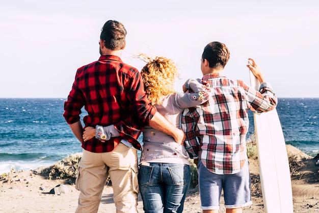 Gelukkige familie knuffelde op het strand kijkend naar de zee of de oceaan met een tiener met een surftafel klaar om te gaan sur
