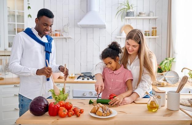 Gelukkige familie kokende groentesalade bij het ontbijt. moeder, vader en hun dochter 's ochtends in de keuken, goede relatie