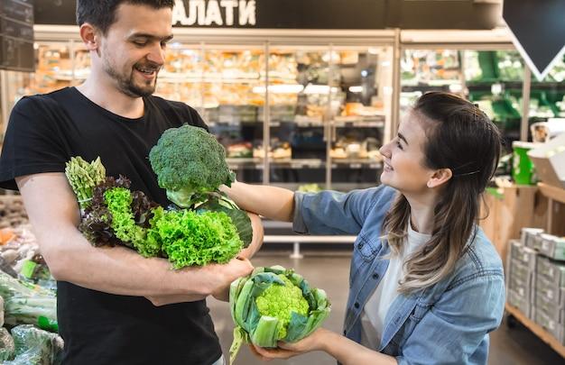 Gelukkige familie koopt groenten. vrolijke familie van drie tomaten in plantaardige afdeling van supermarkt of markt kiezen.