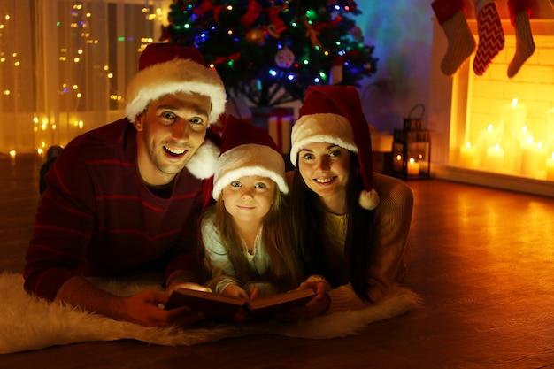 Gelukkige familie leesboek in woonkamer ingericht voor kerstmis