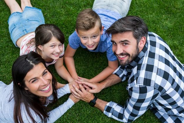 Gelukkige familie liggend op gras in park op een zonnige dag