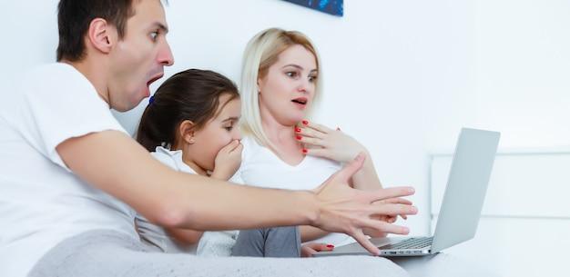 Gelukkige familie ligt op bed en kijkt naar iets op de laptop.