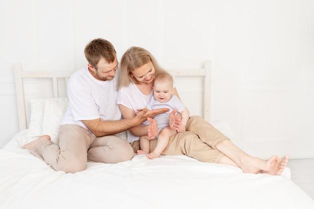 Gelukkige familie mama, papa en baby spelen thuis op het bed en hebben plezier