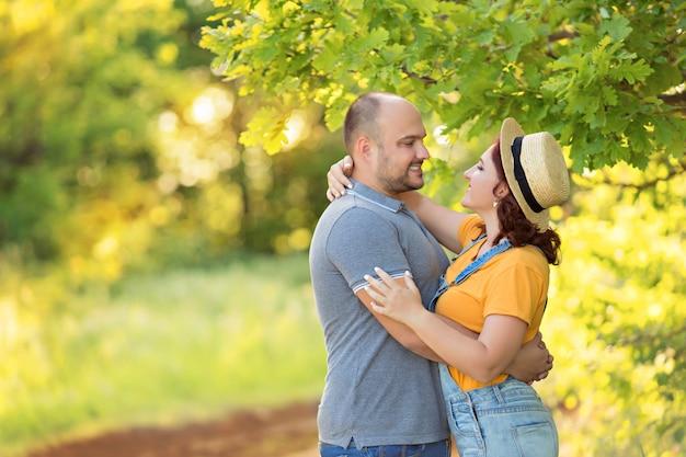 Gelukkige familie, man en vrouw knuffel, kussen elkaar buiten in de zomeravond.