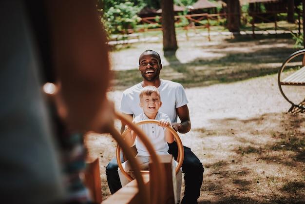 Gelukkige familie mensen spelen wip op speelplaats