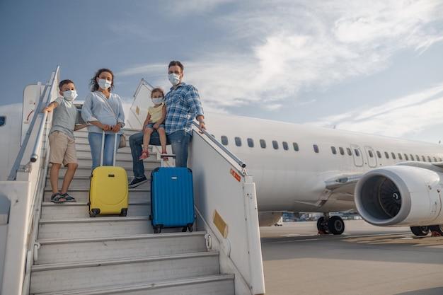 Gelukkige familie met beschermende maskers, ouders met twee kleine kinderen die op de airstair staan, overdag aan boord van het vliegtuig. mensen, reizen, vakantieconcept