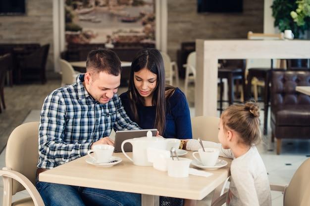 Gelukkige familie met de computer van tabletpc die diner heeft in restaurant
