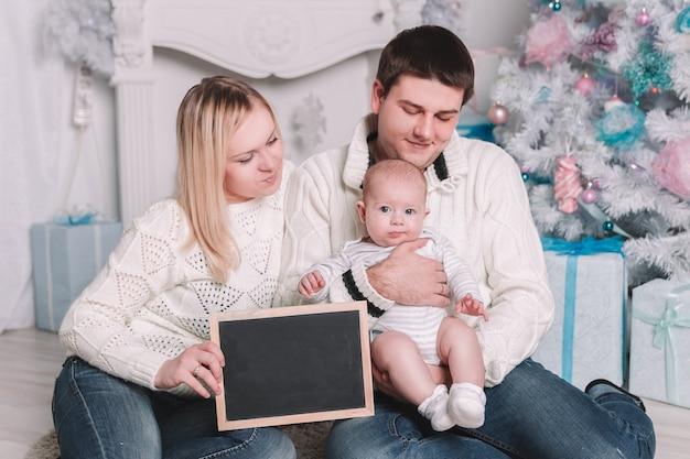 Gelukkige familie met een blanco kerstkaart zittend op het tapijt in een gezellige woonkamer