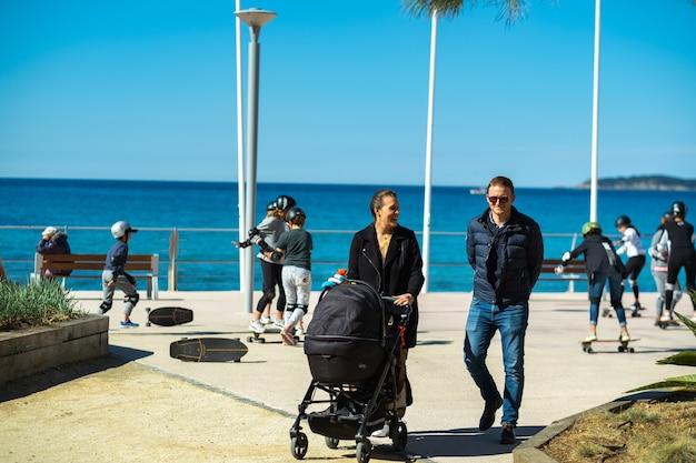 Gelukkige familie met een kinderwagen die langs de promenade loopt