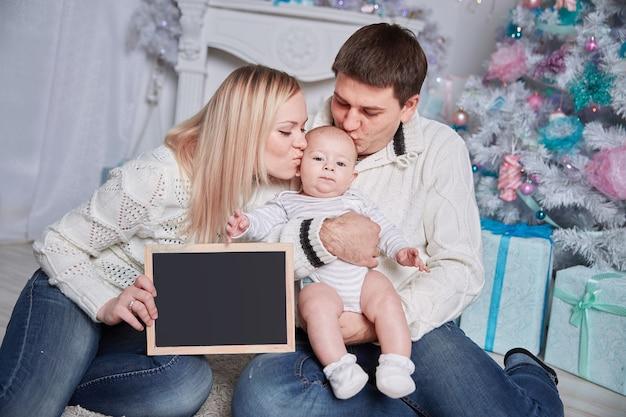 Gelukkige familie met een lege kerstkaart, zittend op het tapijt in een gezellige woonkamer.