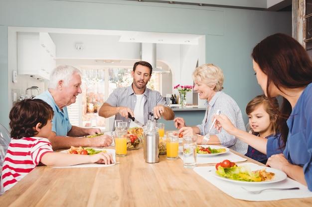 Gelukkige familie met grootouders zitten aan eettafel