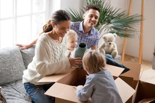 Gelukkige familie met jonge geitjes uitpakkende dozen die zich in nieuw huis bewegen