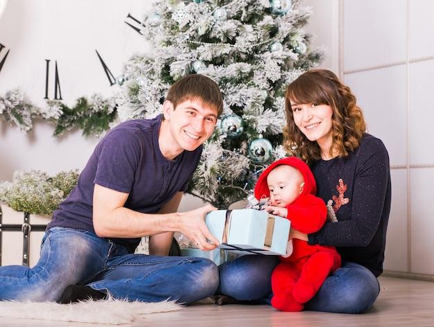 Gelukkige familie met kerstcadeaus in de buurt van de kerstboom. kind, moeder en vader hebben plezier thuis.