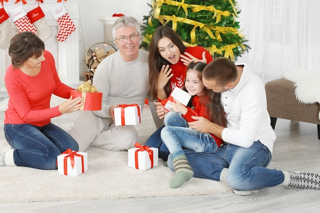 Gelukkige familie met kerstcadeautjes in de woonkamer